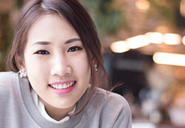 Asian woman smiling wearing a gray shirt